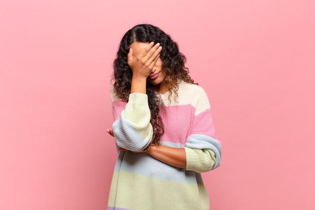 Jonge spaanse vrouw die er gestrest, beschaamd of overstuur uitziet, met hoofdpijn, gezicht bedekt met hand