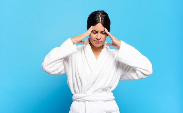 Jonge spaanse vrouw die er gestrest en gefrustreerd uitziet, onder druk werkt met hoofdpijn en last heeft van problemen. badjas concept