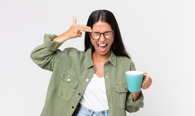 Jonge spaanse vrouw die er ongelukkig en gestrest uitziet, zelfmoordgebaar maakt een pistoolteken en houdt een koffiemok vast