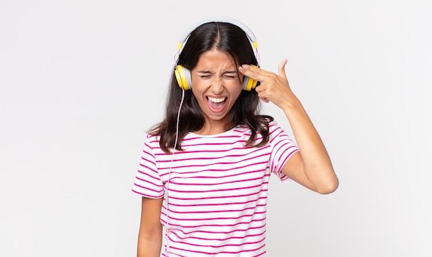 Jonge spaanse vrouw die er ongelukkig en gestrest uitziet, zelfmoordgebaar maakt een pistoolteken en luistert naar muziek met een koptelefoon