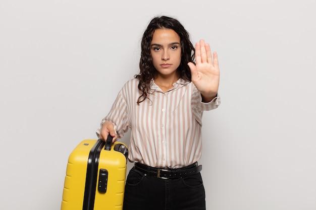 Jonge spaanse vrouw die er serieus, streng, ontevreden en boos uitziet met een open palm die een stopgebaar maakt