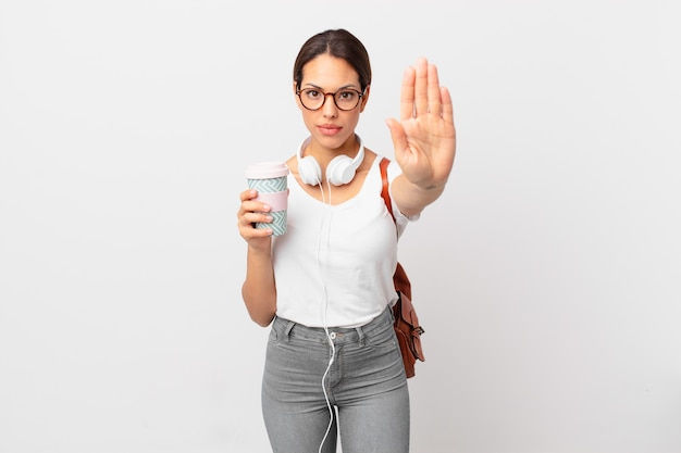 Jonge spaanse vrouw die er serieus uitziet en open palm toont die een stopgebaar maakt. studentenconcept