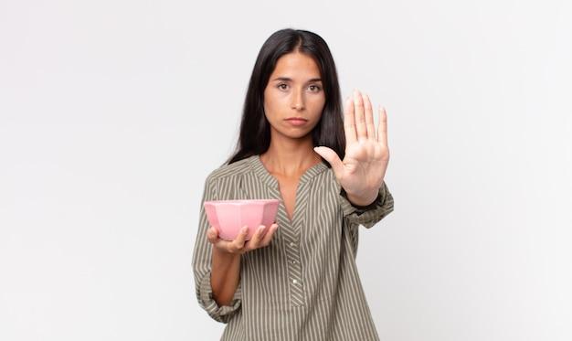 Jonge spaanse vrouw die er serieus uitziet met open palm die een stopgebaar maakt en een lege kom of pot vasthoudt