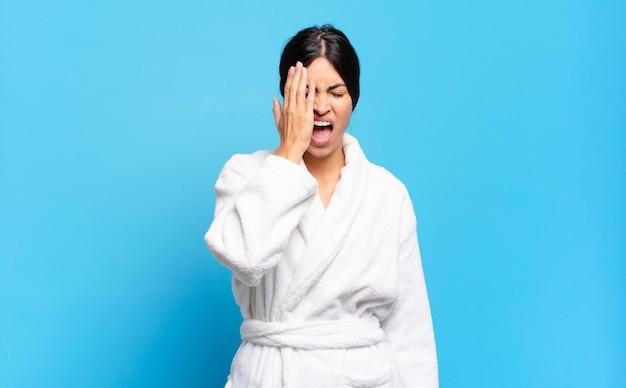 Jonge spaanse vrouw die er slaperig, verveeld en geeuwend uitziet, met hoofdpijn en een hand die de helft van het gezicht bedekt. badjas concept