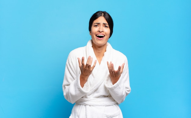 Jonge spaanse vrouw die er wanhopig en gefrustreerd, gestrest, ongelukkig en geïrriteerd uitziet, schreeuwend en schreeuwend. badjas concept