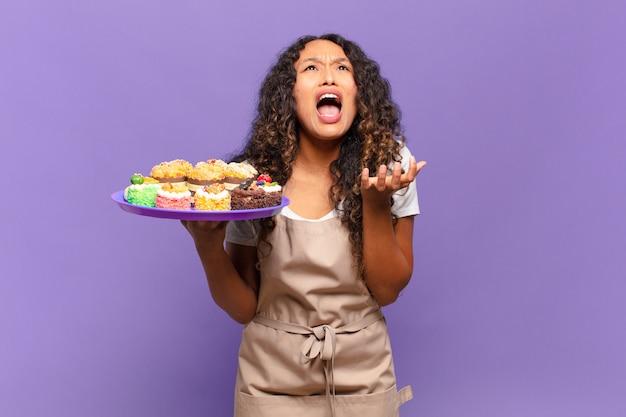 Jonge spaanse vrouw die er wanhopig en gefrustreerd, gestrest, ongelukkig en geïrriteerd uitziet, schreeuwend en schreeuwend. koken taarten concept