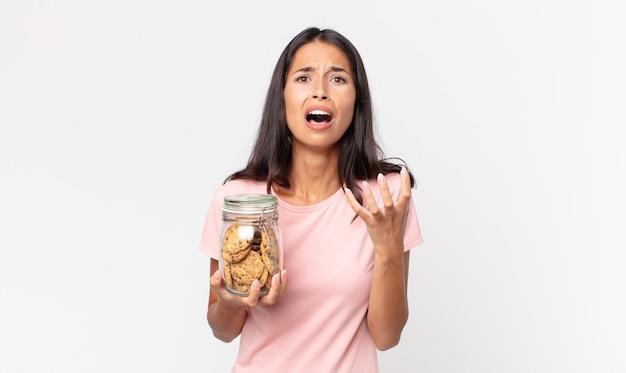 Jonge spaanse vrouw die er wanhopig, gefrustreerd en gestrest uitziet en een glazen fles met koekjes vasthoudt