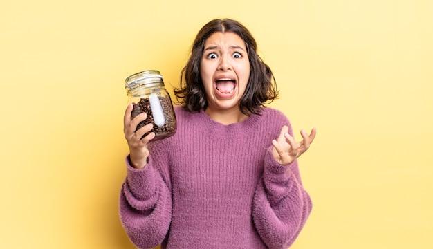 Jonge spaanse vrouw die er wanhopig, gefrustreerd en gestrest uitziet. koffiebonen concept