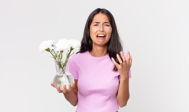 Jonge spaanse vrouw die er wanhopig, gefrustreerd en gestrest uitziet met decoratieve bloemen