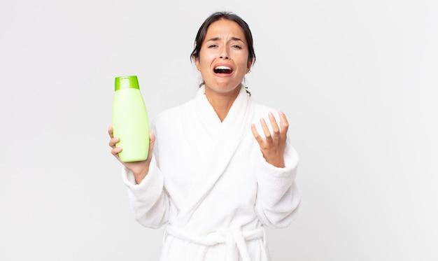 Jonge spaanse vrouw die er wanhopig, gefrustreerd en gestrest uitziet terwijl ze een badjas draagt en een shampoo vasthoudt