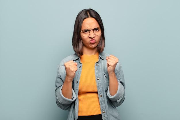 Jonge spaanse vrouw die er zelfverzekerd, boos, sterk en agressief uitziet, met vuisten klaar om te vechten in bokspositie