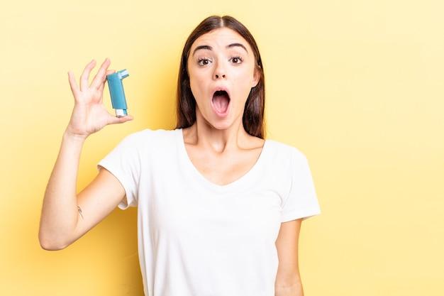 Jonge spaanse vrouw die erg geschokt of verrast kijkt. astma concept