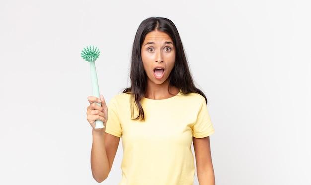 Jonge spaanse vrouw die erg geschokt of verrast kijkt en een afwasborstel vasthoudt