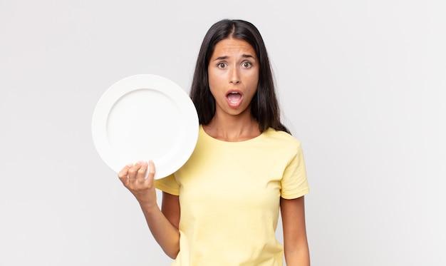 Jonge spaanse vrouw die erg geschokt of verrast kijkt en een leeg bord vasthoudt