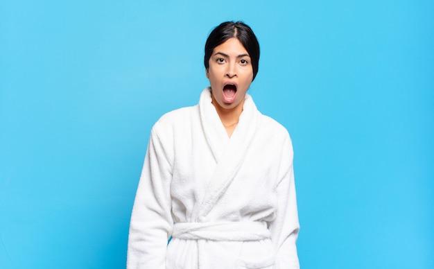 Jonge spaanse vrouw die erg geschokt of verrast kijkt, met open mond staart en wauw zegt. badjas concept
