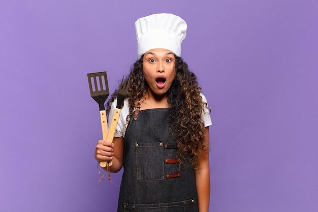 Jonge spaanse vrouw die erg geschokt of verrast kijkt, starend met open mond en zegt wow. barbecue chef-kok concept