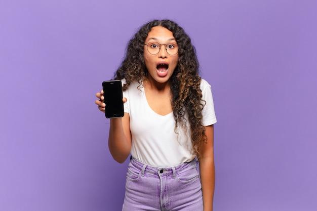 Jonge spaanse vrouw die erg geschokt of verrast kijkt, starend met open mond en zegt wow. slimme telefoon concept