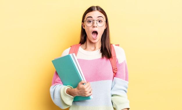 Jonge spaanse vrouw die erg geschokt of verrast kijkt. studentenconcept