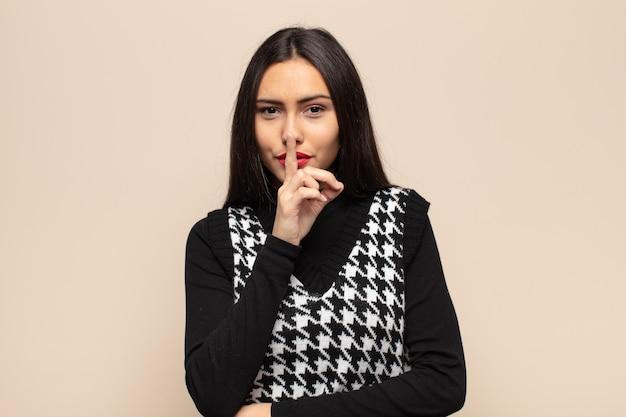 Jonge spaanse vrouw die ernstig en kruis met vinger tegen lippen wordt gedrukt die stilte of stilte eist, een geheim bewaren