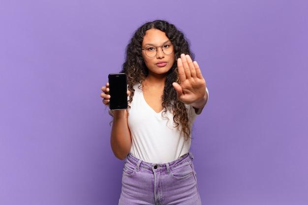 Jonge spaanse vrouw die ernstig, streng, ontevreden en boos kijkt die open palm toont die stopgebaar maakt