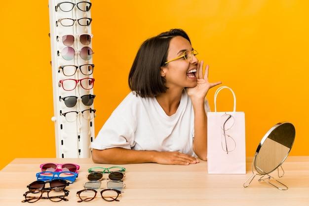 Jonge spaanse vrouw die geïsoleerde glazen probeert te schreeuwen en palm dichtbij geopende mond te houden