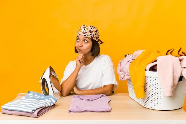 Jonge spaanse vrouw die geïsoleerde kleren strijken zijwaarts kijkt met twijfelachtige en sceptische uitdrukking.