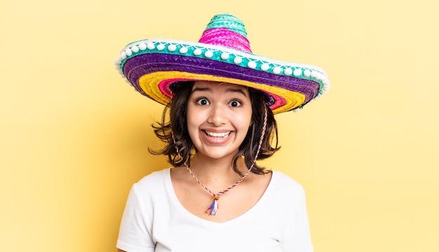 Jonge spaanse vrouw die gelukkig en aangenaam verrast kijkt. mexicaanse hoed concept