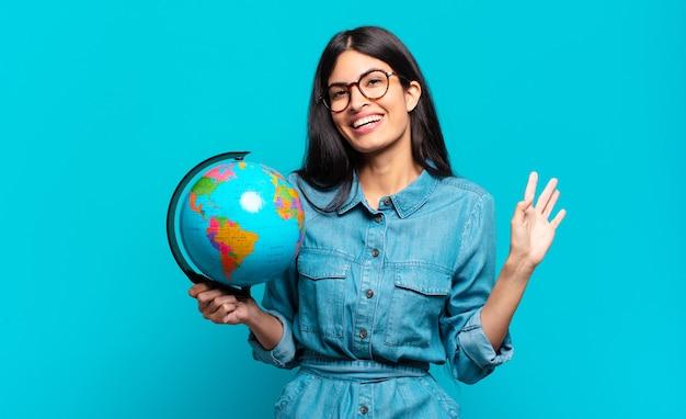 Jonge spaanse vrouw die gelukkig en opgewekt glimlacht, hand zwaait, u verwelkomt en begroet, of afscheid neemt. aarde planeet concept