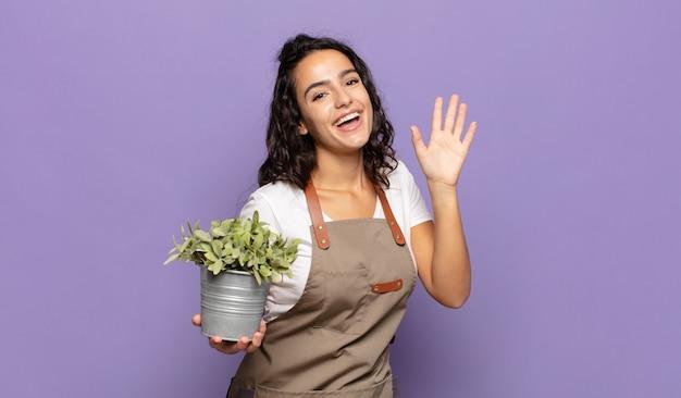 Jonge spaanse vrouw die gelukkig en opgewekt glimlacht, hand zwaait, u verwelkomt en begroet, of afscheid neemt