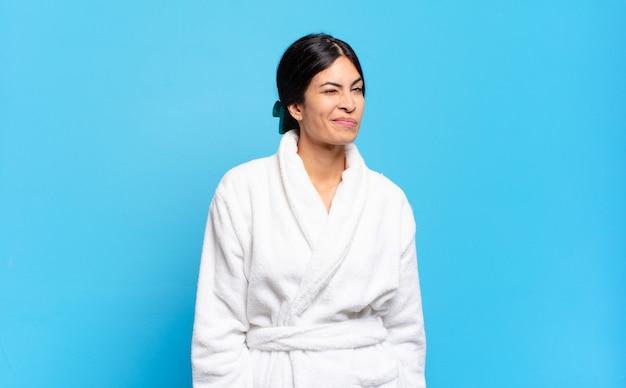 Jonge spaanse vrouw die gelukkig en vriendelijk kijkt, glimlachend en met een positieve houding naar je knipoogt. badjas concept