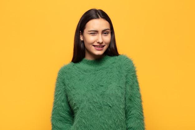 Jonge spaanse vrouw die gelukkig en vriendelijk kijkt, glimlachend en met een positieve houding naar je knipoogt