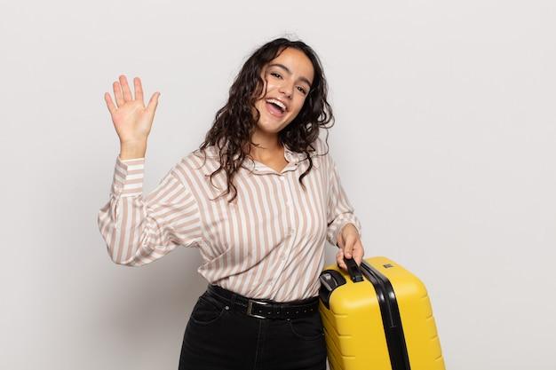 Jonge spaanse vrouw die gelukkig en vrolijk glimlacht, golvende hand