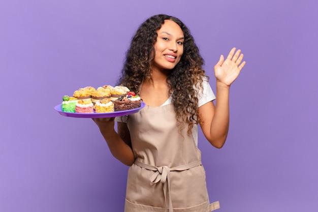 Jonge spaanse vrouw die gelukkig en vrolijk glimlacht, met de hand zwaait, u verwelkomt en begroet, of afscheid neemt. koken taarten concept