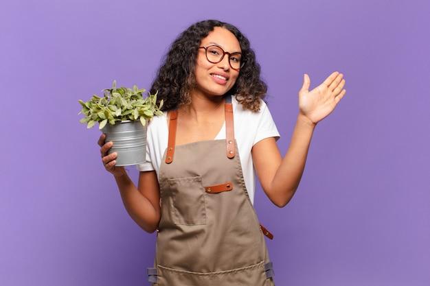 Jonge spaanse vrouw die gelukkig en vrolijk glimlacht, met de hand zwaait, u verwelkomt en begroet, of afscheid neemt. tuin keeper concept