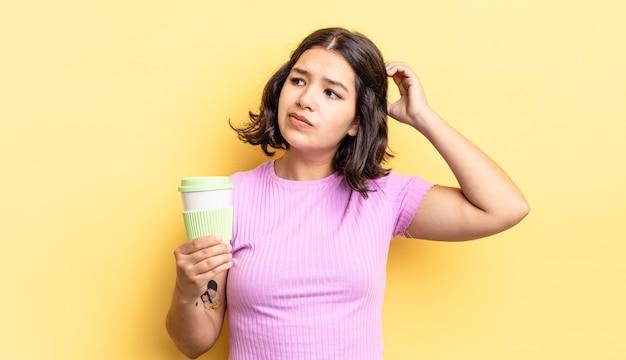 Jonge spaanse vrouw die gelukkig glimlacht en dagdroomt of twijfelt. afhaal koffie concept
