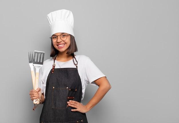 Jonge spaanse vrouw die gelukkig glimlacht met een hand op de heup en een zelfverzekerde, positieve, trotse en vriendelijke houding
