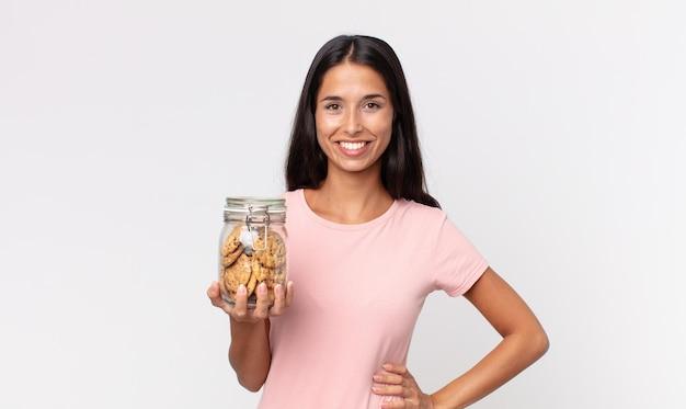 Jonge spaanse vrouw die gelukkig glimlacht met een hand op de heup en zelfverzekerd en een glazen fles met koekjes vasthoudt