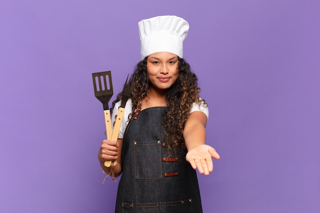 Jonge spaanse vrouw die gelukkig glimlacht met een vriendelijke, zelfverzekerde, positieve blik, een object of concept aanbiedt en toont. barbecue chef-kok concept