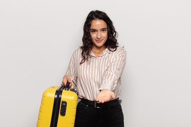 Jonge spaanse vrouw die gelukkig glimlacht met vriendelijke, zelfverzekerde, positieve blik, die een voorwerp of concept aanbiedt en toont