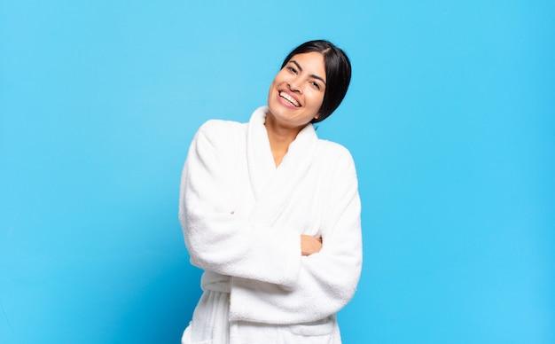 Jonge spaanse vrouw die gelukkig lacht met gekruiste armen, met een ontspannen, positieve en tevreden pose