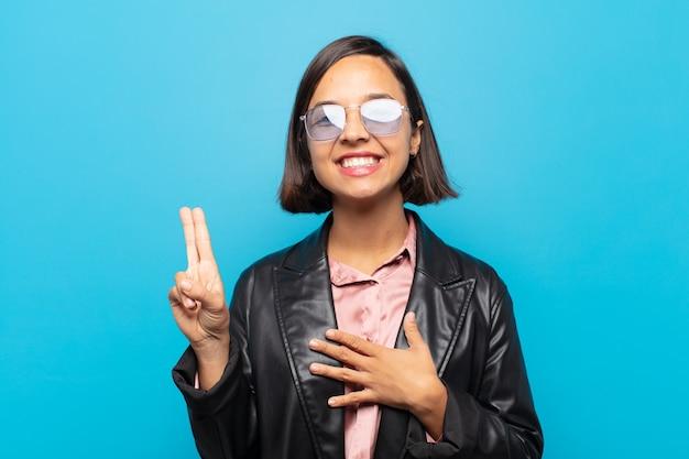 Jonge spaanse vrouw die gelukkig, zelfverzekerd en betrouwbaar kijkt, glimlachend en overwinningsteken toont, met een positieve instelling