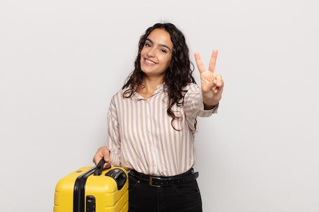 Jonge spaanse vrouw die gelukkig, zorgeloos en positief glimlacht en kijkt, overwinning of vrede met één hand gebaren