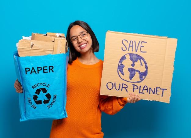 Jonge spaanse vrouw die gerecycled papier vasthoudt en ons planeetbord redt