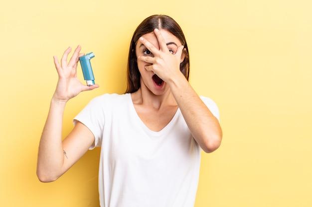 Jonge spaanse vrouw die geschokt, bang of doodsbang kijkt en haar gezicht bedekt met de hand. astma concept