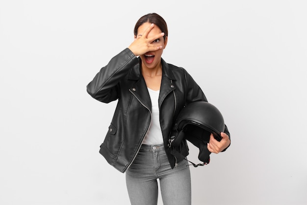 Jonge spaanse vrouw die geschokt, bang of doodsbang kijkt en haar gezicht bedekt met de hand. motorrijder concept