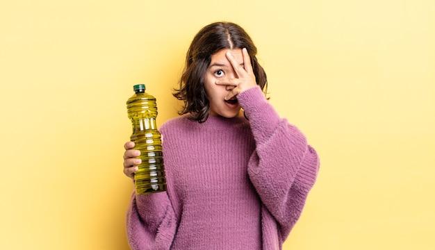 Jonge spaanse vrouw die geschokt, bang of doodsbang kijkt en haar gezicht bedekt met de hand. olijfolie concept