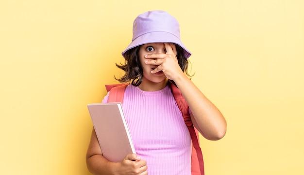 Jonge spaanse vrouw die geschokt, bang of doodsbang kijkt en haar gezicht bedekt met de hand. terug naar schoolconcept