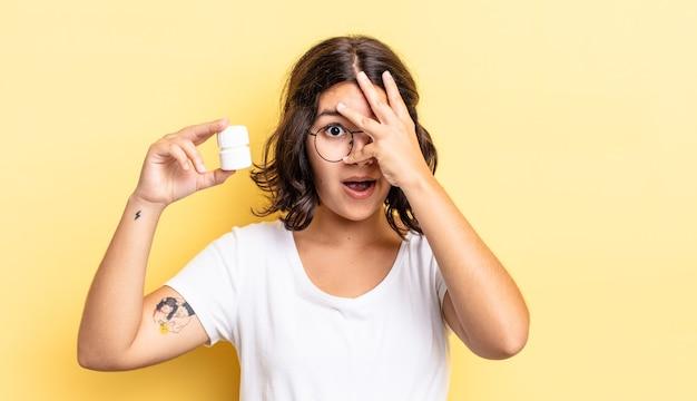 Jonge spaanse vrouw die geschokt, bang of doodsbang kijkt en haar gezicht bedekt met de hand. ziekte pillen concept