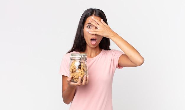 Jonge spaanse vrouw die geschokt, bang of doodsbang kijkt, haar gezicht bedekt met de hand en een glazen fles met koekjes vasthoudt