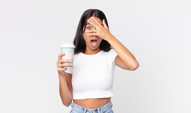Jonge spaanse vrouw die geschokt, bang of doodsbang kijkt, haar gezicht bedekt met de hand en een koffiebeker vasthoudt